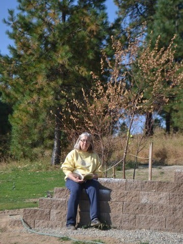 A woman sitting outside with a book in her hands.