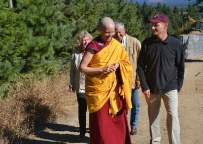 Buddhist nun, Venerable Tarpa walking beside a man, while a man and a woman walks behind them.