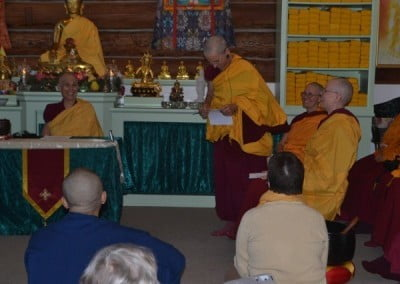 Buddhist nun, Venerable Semkye standing and looking at a piece of paper, other buddhist nuns sitting are laughing.
