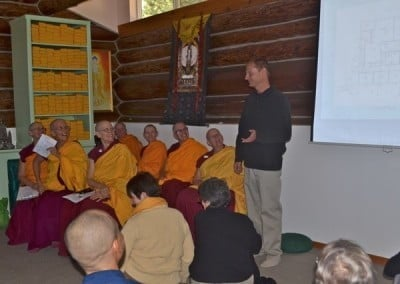 A man standing while abbey sangha who are sitting on chairs are looking at him when he talks.