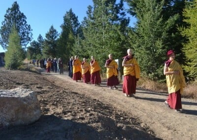 Buddhist nun, Venerable Chodron walking in front while the abbey sangha and lay people walk behind her down a slope.