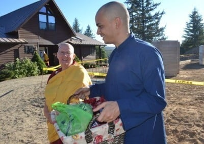Anagarika, Jack taking a basket of gifts while Venerable Jigme looks at him.