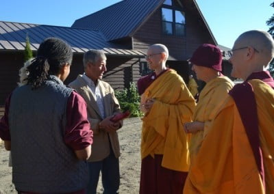 Three buddhist nuns talking to a man who is holding a gift in his hands, just outside Ananda Hall