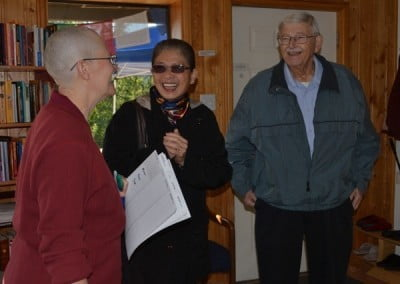 Buddhist nun, Venerable Chonyi smiling happily at a man and a woman.