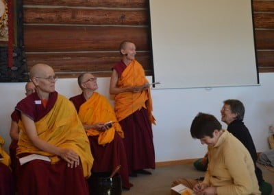 Buddhist nun, Venerable Samten standing at the back holding some paper in her hands.