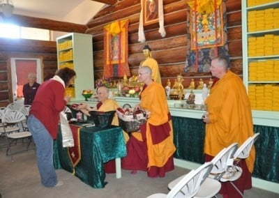 Buddhist nun, Venerable Chodron holding a gift in her hands and passing it to a woman.