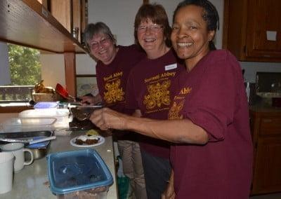 Three women preparing food in the kitchen.