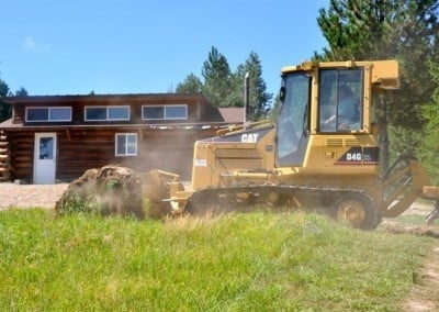 A man operating a bulldozer that is removing the topsoil.