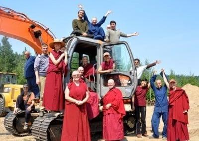 Abbey sangha, anagarikas, men and women posing with the earthmover.