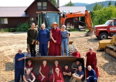 Some buddhist nuns, men and women sitting inside the front loader of the bulldozer, some standing on top of the front loader.