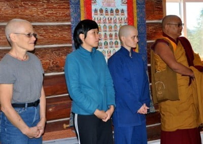 Two women, an anagarika and a buddhist monk standing and looking.