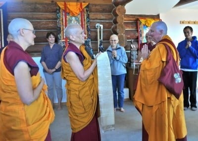 Buddhist nun, Venerable Chodron holding a khata in her hands, buddhist nun Venerable Thubten Tsultrim in praying gesture looking at her.