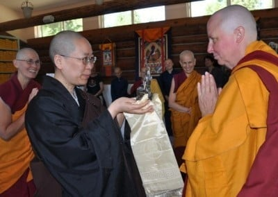 Chinese nun, Venerable Jendy holding a khata and buddha statue in her hands, buddhist nun Venerable Thubten Tsultrim in praying gesture looking at her.