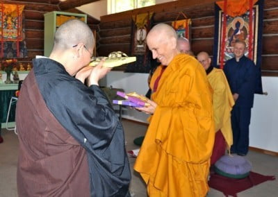 Chinese nun, Venerable Jendy holding a gift in her hands and buddhist nun, Venerable Chodron smiling and looking at the two gifts in her hands.
