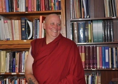 A smiling buddhist nun, Venerable Tsultrim standing in front of bookcases.