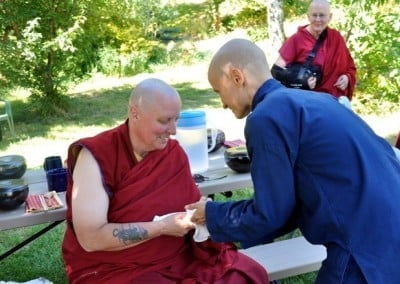 Anagarika, Dani giving an offering to Buddhist nun, Venerable Tsultrim who is sitting on a bench.