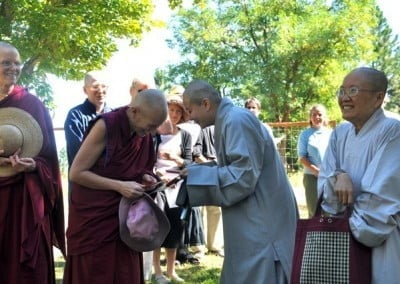 A Chinese nun giving an offering to buddhist nun, Venerable Chodron, everyone full of smiles.