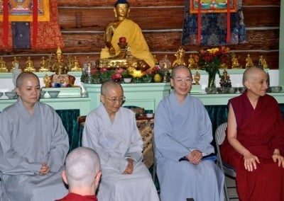Buddhist nun, Venerable Chodron and Chinese nuns sitting in a straight row in front of the Buddha statue.