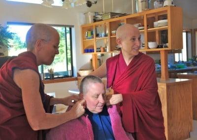 Buddhist nuns, Venerable Chodron and Venerable Semkye putting a towel on anagarika, Terri's neck.