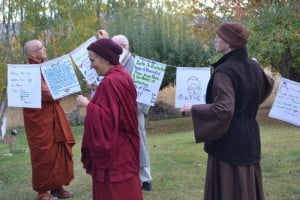 Venerable Thubten Chodron (left), abbot of of Sravasti Abbey, helps hang prayers flags to bless Sravasti Abbey's land.
