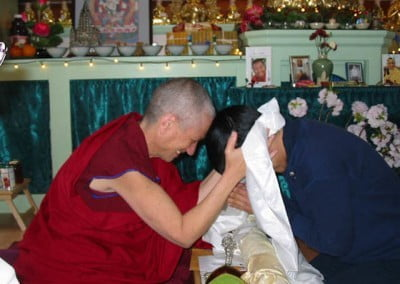 Venerable touches foreheads with one of the retreatants in a traditional Tibetan sign of affection.