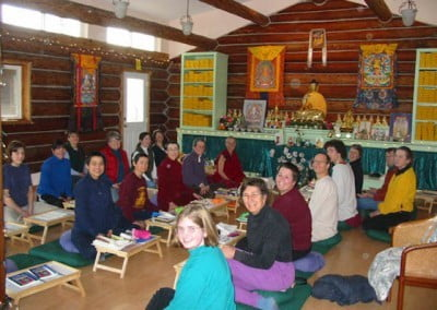 The group poses for a photos in the meditation hall, lined up in rows facing each other and seated behind their puja tables