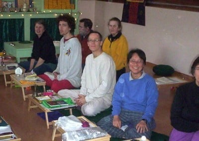 Retreatants sit with their puja tables in the Meditation Hall and pose for a photo