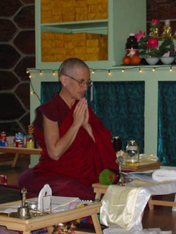 Venerable Chodron sits behind her puja table and offers prayers with hands together.
