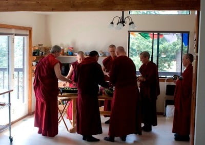 The sangha gather in the new serving area. This new part of the kitchen remodel helps the flow of people and makes the food serving more efficient.