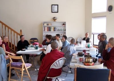 Monastics and lay sit around several tables in the dining room while Venerable Chodron answers their questions
