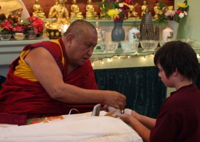 Nick, the youngest participant at the teachings, receives a gift from Rinpoche.