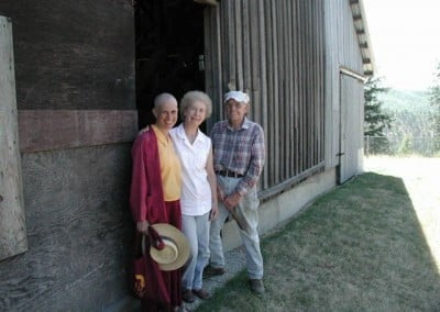 Venerable Chodron poses for a photo at the barn with Vicki and Harold Unruh who are the previous owners. They cared for the house, garden, meadows, and forest with a lot of love.
