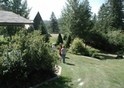 Vicki and Ven. Chodron walk through the garden towards the barn.
