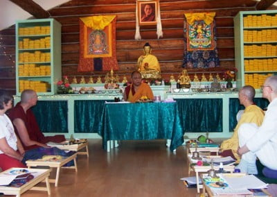 Geshe Damdul sits at the front of the meditation hall and leads 2 perpendicular rows of participants in the tsog