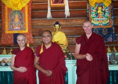 Three monastics pose for a photo in front of the alter in the meditation hall