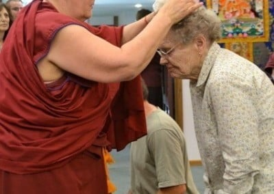 Venerable Jigme places the relics on the head of a participant.