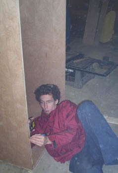 A man lays on the ground with a measuring tape and pencil to mark a piece of wood.