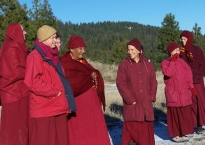 Maroon robes against the deep blue sky. The monastics with Khensur Rinpoche stood where the Abbey temple will one day be built.