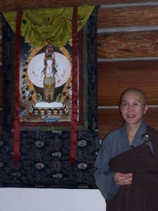 Bhikshuni Jen-cha stands beside the  beautiful Chenrezig thangka in the  meditation hall.