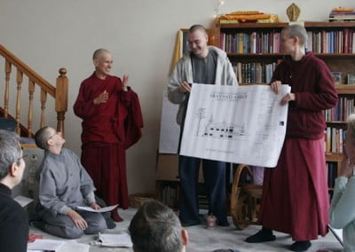 Venerable Tarpa and Carl hold up a drawing of what the new monastic residence will look like, while others sit in a circle on the floor and watch.