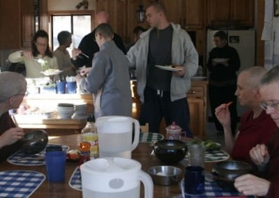A kitchen full of guests and residents, some sitting and eating, some dishing food onto their plates.