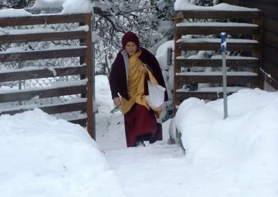 Venerable Chodron walks along a snowy path