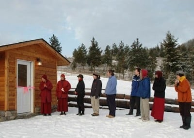 Venerable Chodron and guests line up single file in front of the meditation hall.