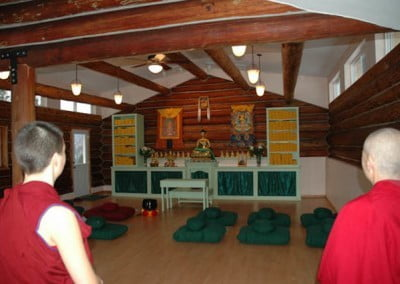 Venerable Chodron and Venerable Jampa enter an otherwise empty hall.
