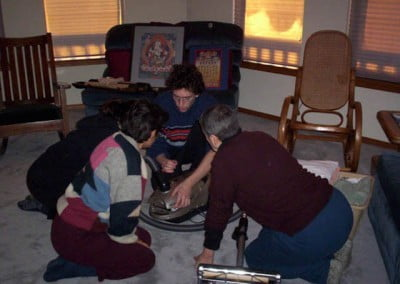 Three retreatants sit on the floor listing to a fourth retreatant show them how to use a vacuum cleaner that sits between them.