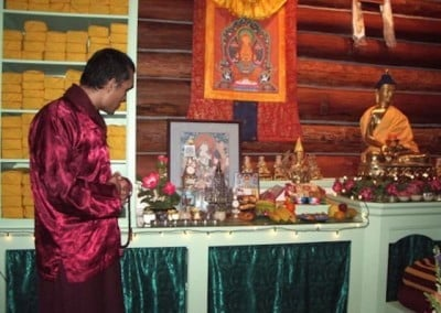 Yangsi Rinpoche stands in front of the Meditation Hall altar and admires the statue of the stupa at Bodhgaya that was given to the Abbey by Amitabha Buddhist Centre in Singapore.