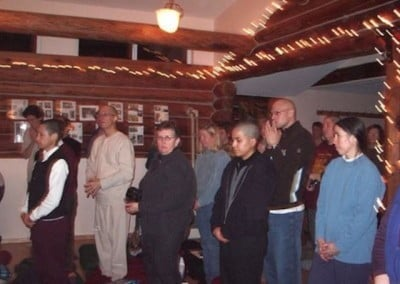 Monastics, retreatants, and guests wait in the meditation hall before Rinpoche enters.