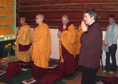 Monastics standing and waiting in the meditation hall before Rinpoche enters.