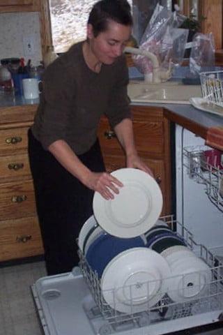 A woman loads the dishwasher