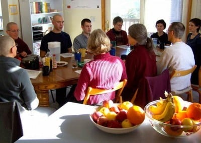 Retreatants sit around the dining room table and offer prayers before the meal
